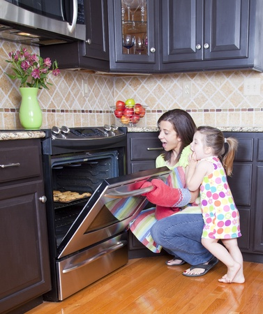 Pretty woman opening oven with a tray of cookies