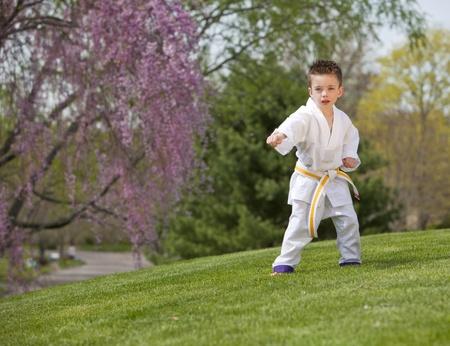 oefenen: Jonge jongen het beoefenen van vechtsporten buiten in het voorjaar