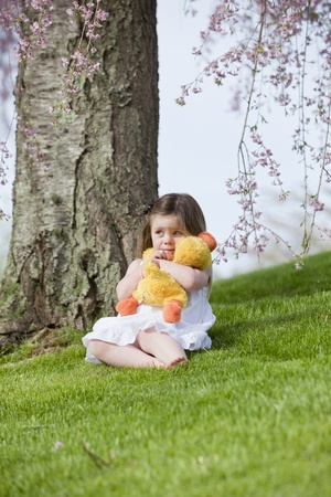 Sad little girl with her toy sitting under a tree