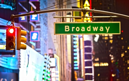 Broadway sign and red stop light in New York City at night