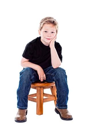 Cute boy in studio sitting on a stool photo
