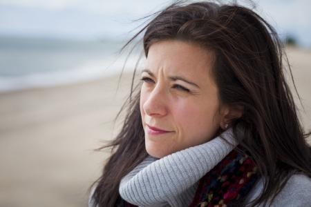 Doordachte mooie vrouw op het strand met uitzicht op zee