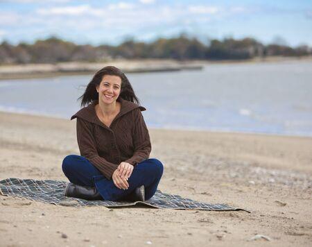 Pretty woman sitting alone at a empty beach Stock Photo - 11560575