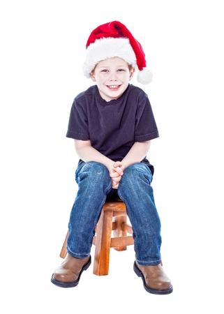 Cute happy boy wearing a santa hat studio portrait photo