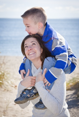 shoulder ride: Mother giving son a shoulder ride at the beach