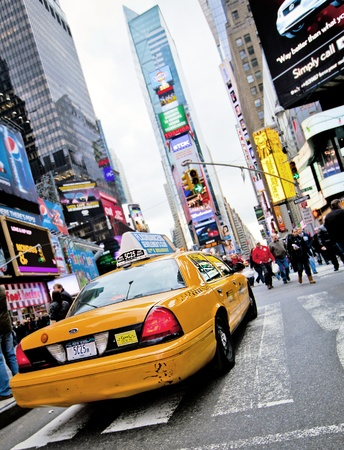 NEW YORK - DECEMBER 17: Yellow cab speeds through Times Square the busy tourist intersection of neon art and commerce and is an iconic street of New York City on Dec 17th, 2009 in New York, NY, USA. Reklamní fotografie - 12160339
