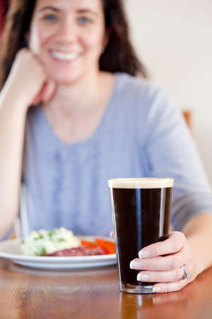 Young woman holding a pint with lunch at a pub photo