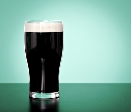 Pint of Irish beer on a green background photo