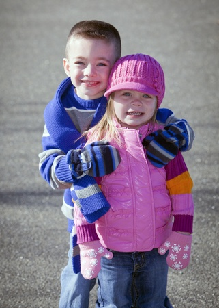 Cute brother and sister in winter hugging outside photo