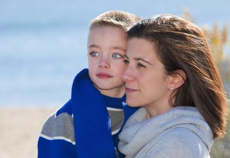 shoulder ride: Madre hijo dando un paseo en el hombro en la playa Foto de archivo
