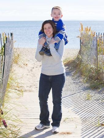 Madre hijo dando un paseo en el hombro en la playa