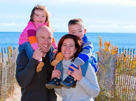 Family of four at the beach in winter portrait  photo