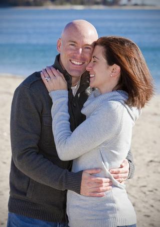 hombre calvo: Abrazos guapo joven pareja en la playa en invierno