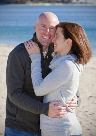 Handsome young couple hugging at the beach in winter  photo