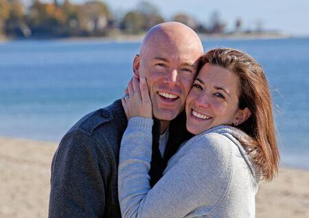 bald man: Abrazos guapo joven pareja en la playa en invierno
