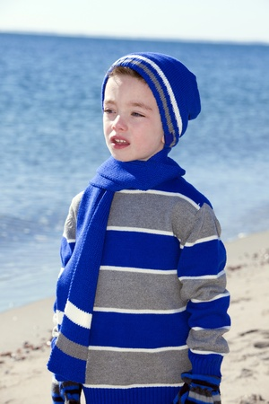 Young boy at the beach wearing winter clothing photo