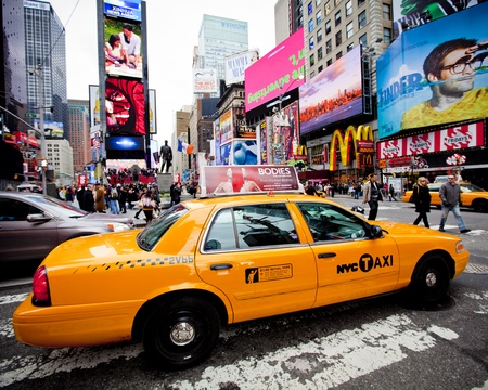 NEW YORK - DECEMBER 17: Yellow cab speeds through Times Square the busy tourist intersection of neon art and commerce and is an iconic street of New York City on Dec 17th, 2011 in New York, NY, USA.  新闻类图片