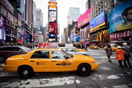 NEW YORK - DECEMBER 17: Yellow cab speeds through Times Square the busy tourist intersection of neon art and commerce and is an iconic street of New York City on Dec 17th, 2011 in New York, NY, USA.  Editoriali
