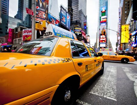 NEW YORK - DECEMBER 17: Yellow cab speeds through Times Square the busy tourist intersection of neon art and commerce and is an iconic street of New York City on Dec 17th, 2011 in New York, NY, USA.  Stock Photo - 12160349