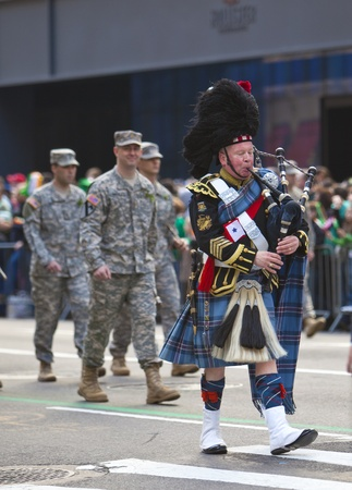NEW YORK, NY, USA MAR 17: Marching US miltary soldier and bagpiper from the 69th Infantry at the St. Patrick's Day Parade on March 17, 2012 in New York City, United States. Stock Photo - 13062581