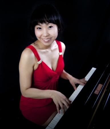 Beautiful asian woman playing the grand paino photo