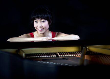 grand piano: Beautiful asian woman playing the grand paino