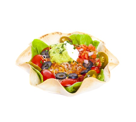 Taco salad in a baked tortilla on white background