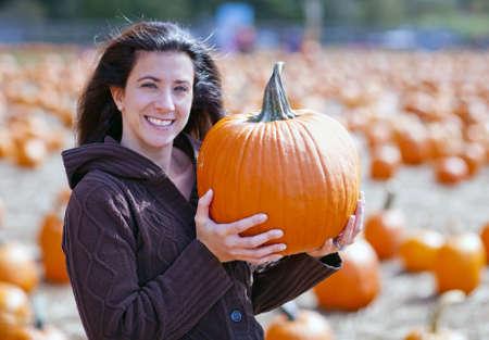 Woman at pumpkin patch selecting a pumpkin