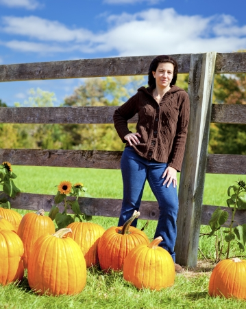 Woman at pumpkin patch selecting a pumpkin photo