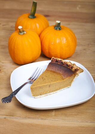 Slice of pumpkin pie on a wooden table photo
