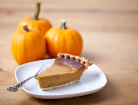 Slice of pumpkin pie on a wooden table