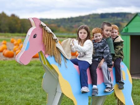 Children playing on a fake wodden horse on a pumpkin farm Archivio Fotografico