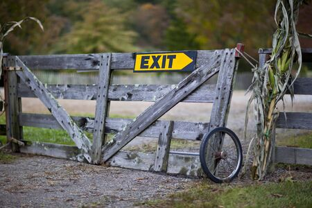 wayout: Old wooden gate on farm with exit direction sign