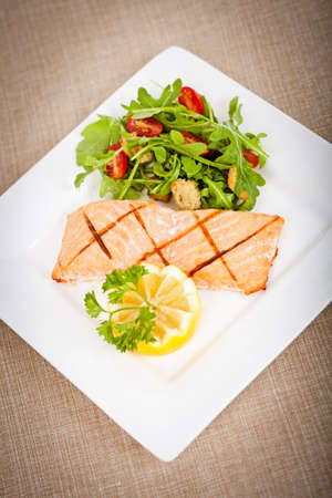 Fresh cooked salmon fillet with arugula salad photo