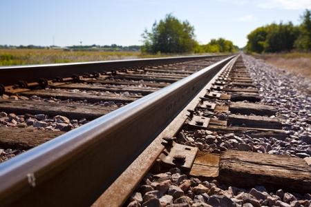 Railroad tracks vanishing into a rural area