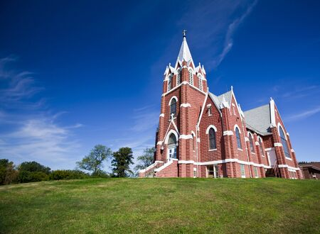 Rural brick christian church set against blue sky