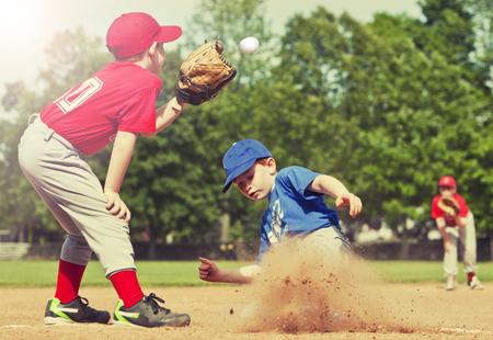 juventud: El muchacho de deslizamiento en la base durante un juego de béisbol con filtro de estilo Instagram