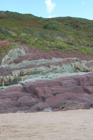 heathland: Portrait view of sand, red rocks, heathland and sky on a Welsh beachfront