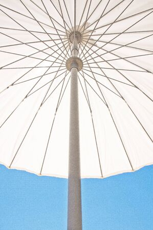 contrasting: A vibrant contrasting Holiday parasol agasint a vivid blue sky