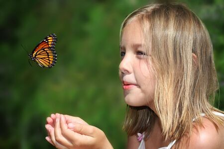 Young girl enjoying spring with a butterfly