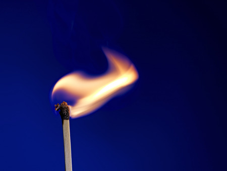 Macro shot of a flaming matchstick on blue photo