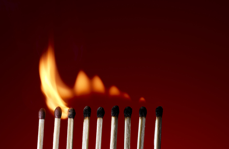 Macro shot of a flaming matchstick on a red background photo