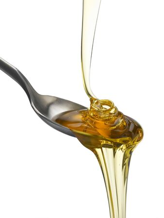 treacle: Golden treacle pouring onto spoon Stock Photo