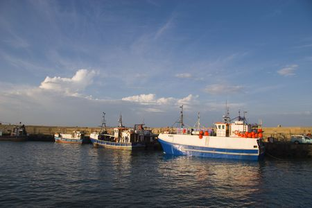 Fishing boats tied to the quay in St Francis Bay harbour preparing to go to sea Stock Photo