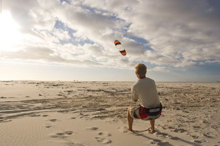 A young man flying a power kite in strong wind photo