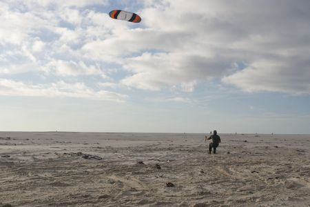 A young man flying a power kite in strong wind