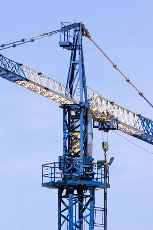A blue and white crane at a construction site photo