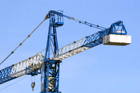 A blue and white crane at a construction site Stock Photo