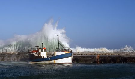 Wave threatening moored fishing boat