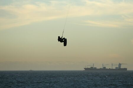 A kite surfer hangs high above the water with a container ship in the background